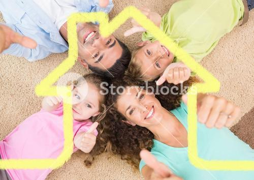 Family laying on the rug at home against house outline in background