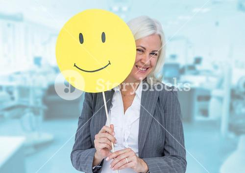 Senior businesswoman holding smiley face against wooden background
