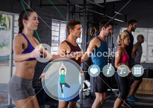Fit people performing jump ropes in gym against fitness interface in background