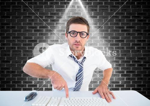 Man in spectacles typing on keyboard against brick wall background