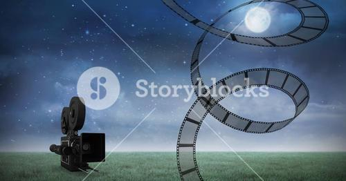 Film reel against video camera and night sky in background