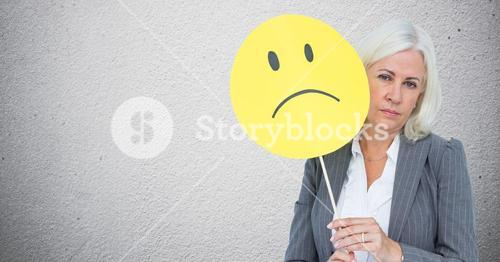 Senior businesswoman holding smiley face against grey background