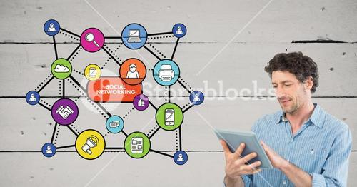 Man using digital tablet against social media icons in background