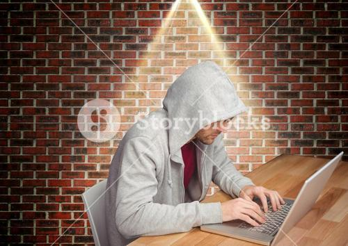Man in hooded top sitting against brick wall and using laptop