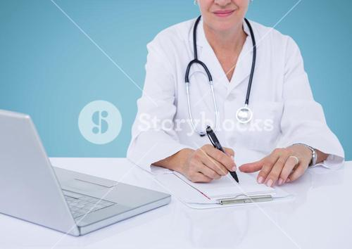 Female doctor sitting at desk with laptop and writing on clipboard