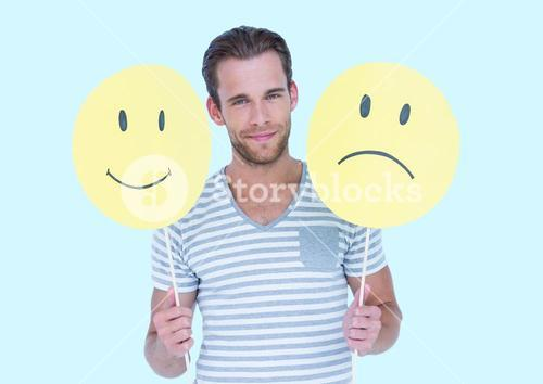 Man holding a smiley face and sad face