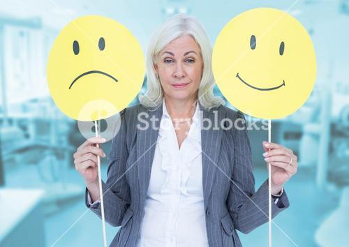 Portrait of a businesswoman holding smiley and sad faces