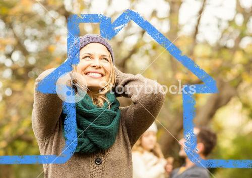 Cheerful woman overlaid with house shape in park