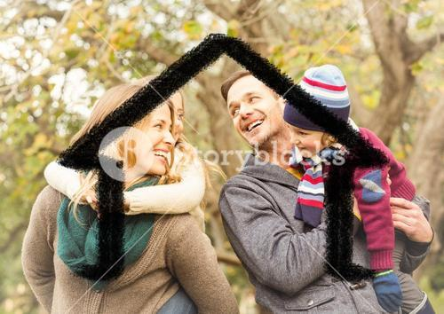 Happy family overlaid with house shape in park