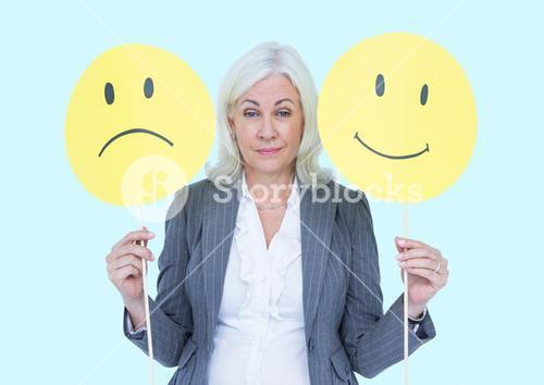 Businesswoman holding smiley and sad faces