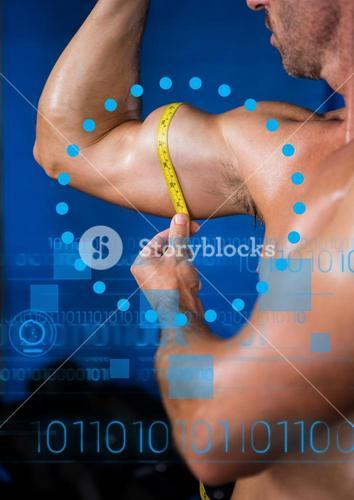 Fit man measuring biceps with measuring tape