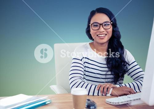 Smiling woman sitting at computer desk