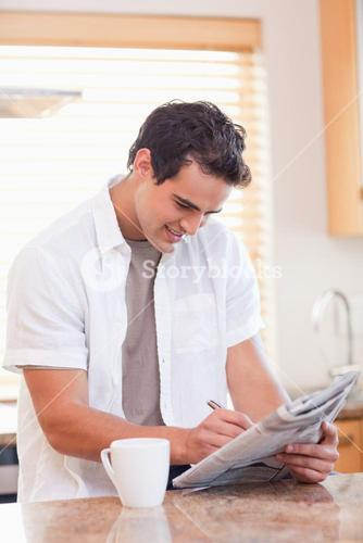 Man solving crossword puzzle in the kitchen