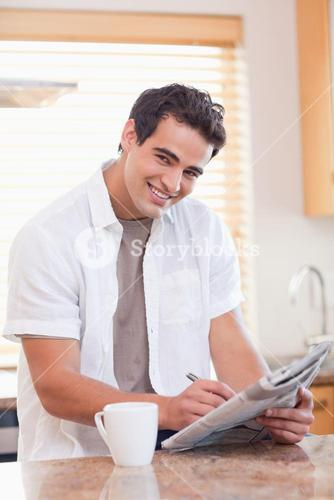 Smiling man doing crossword puzzle in the kitchen
