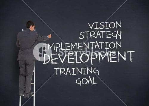 Businessman on ladder writing business terms on blackboard