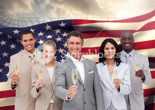 Portrait of group of happy businesspeople holding champagne flutes against American flag