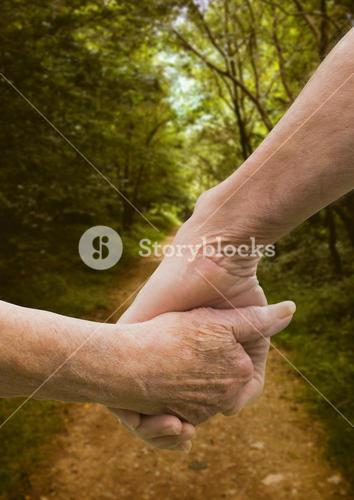 Close-up of couple holding hands against footpath