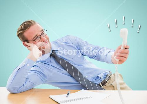 Irritated businessman holding telephone receiver at desk