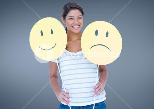 Cheerful woman holding smiley and sad face