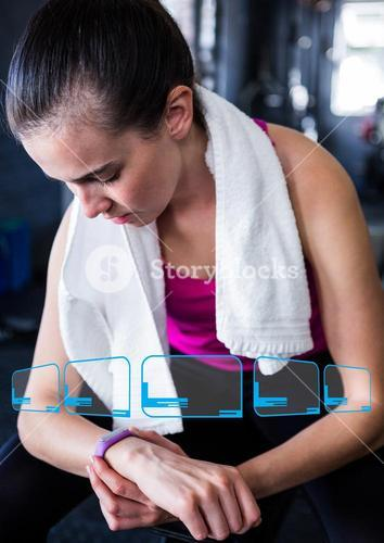 Woman looking at fitness band on wrist in gym