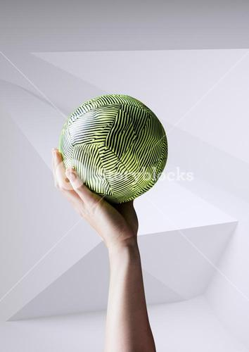 Close-up of hand holding ball against white background