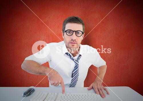 Confused man pointing to computer keyboard at desk