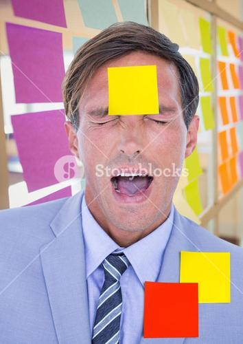 Stressed businessman with sticky notes on forehead