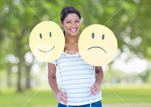Happy woman holding smiley and sad face