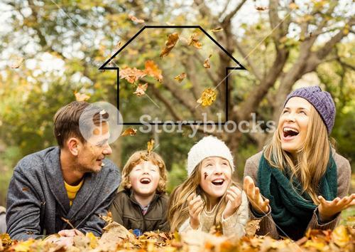Family laying in park with home outline