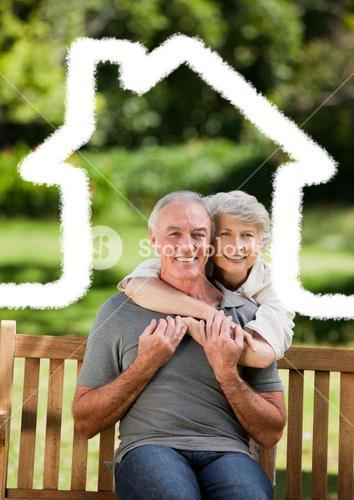 Senior couple sitting in the park with home outline