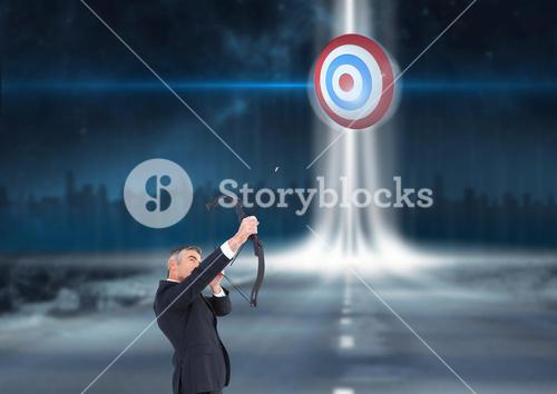 Businessman holding a cross bow and aiming at the target board