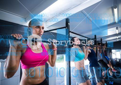Fit people performing pull up exercise in gym