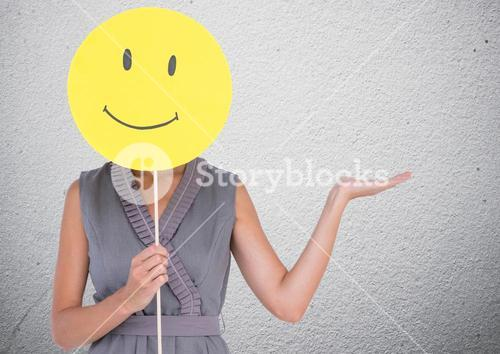 Woman covering her face with smiley and gesturing