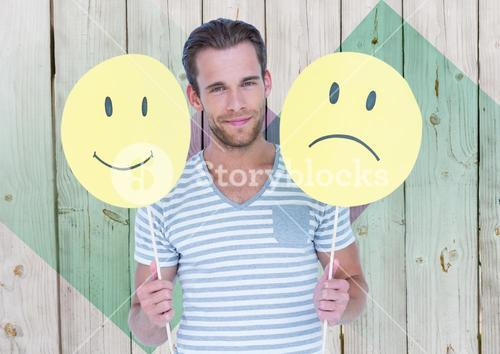 Man holding happy and sad smiley faces