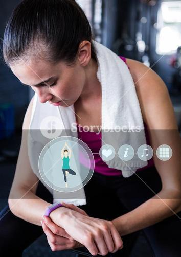 Woman checking her fitness band in gym