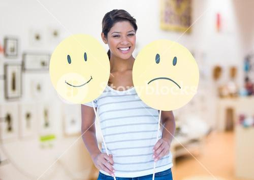 Woman holding happy and sad smiley faces