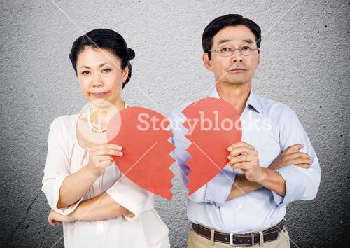 Displeased mature couple holding a broken heart