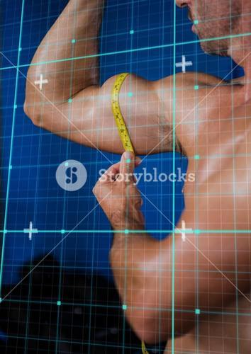 Muscular man measuring his biceps with tape
