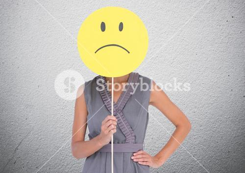 Woman covering her face with sad smiley against concrete background