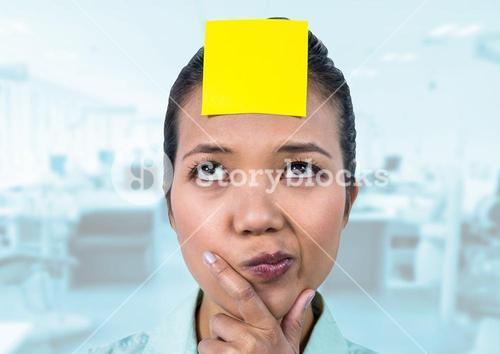 Thoughtful female executive with sticky note on head in office
