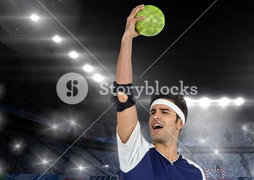 Successful male athlete holding ball in stadium