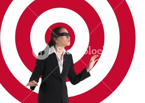 Conceptual image of businesswoman with black band on eyes against archery board