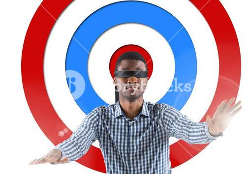 Conceptual image of male executive with black band on eyes against standing archery board