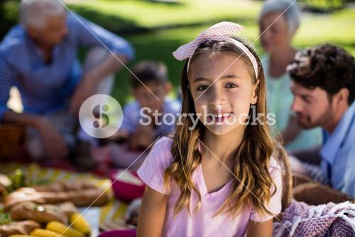Girl with hairband and family enjoying the picnic in background