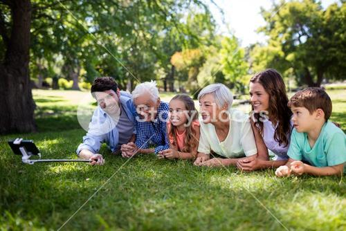 Multi generation family lying on grass and taking a selfie