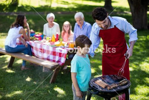 Father and son barbequing in the park