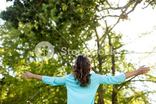 Woman standing with arms wide open in the park