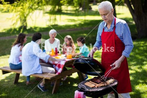 Senior man barbequing with family in background