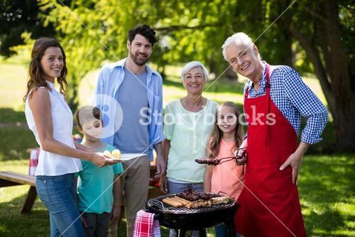 Multi generation family standing near the barbeque in park