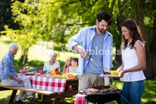 Couple preparing barbeque in park